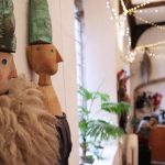 """Two wooden puppets in focus. They are Hansel and Grettel. They are rosy cheeked and blue eyed with """"hats"""" made from half baguettes. The background is blurred but shows strings of fairy lights in the top right corner, an office desk and a leafy indoor plant on a window ledge."""